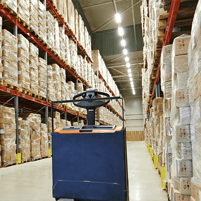 A blue machine in storage room filled with packages