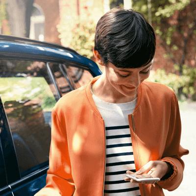Kvinna med orange jacka ler och kollar ner mot sin mobil