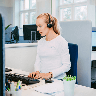 Blonde girl working at a computer with a headset on