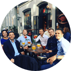 well dressed People sitting outside a bar smiling and drinking